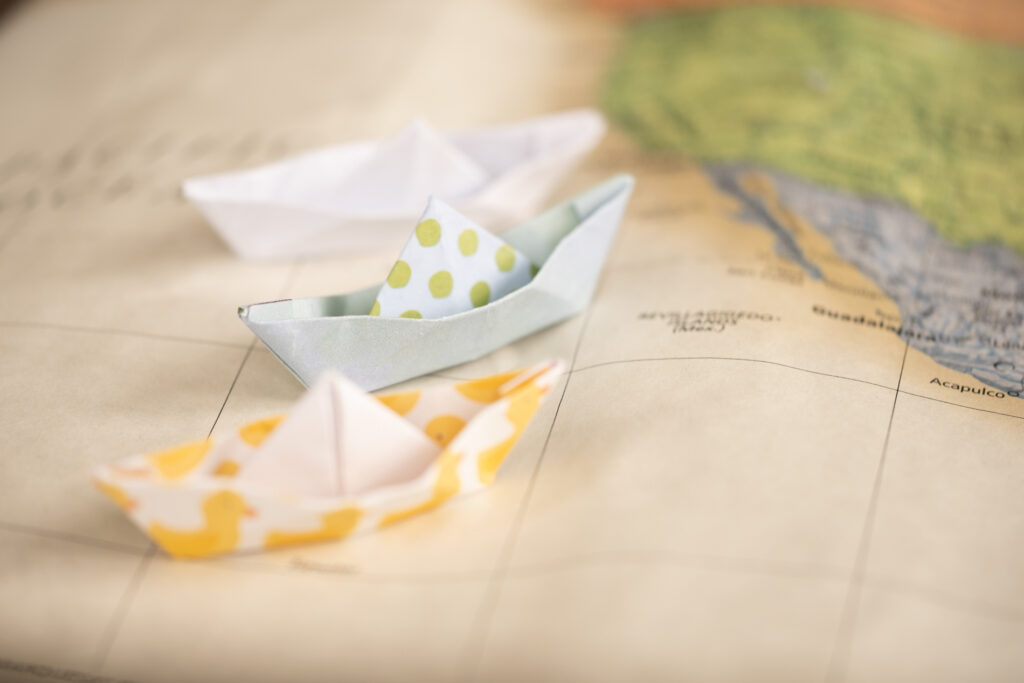 paper boats sailing in the Pacific Ocean off the west coast of North America on a paper map.