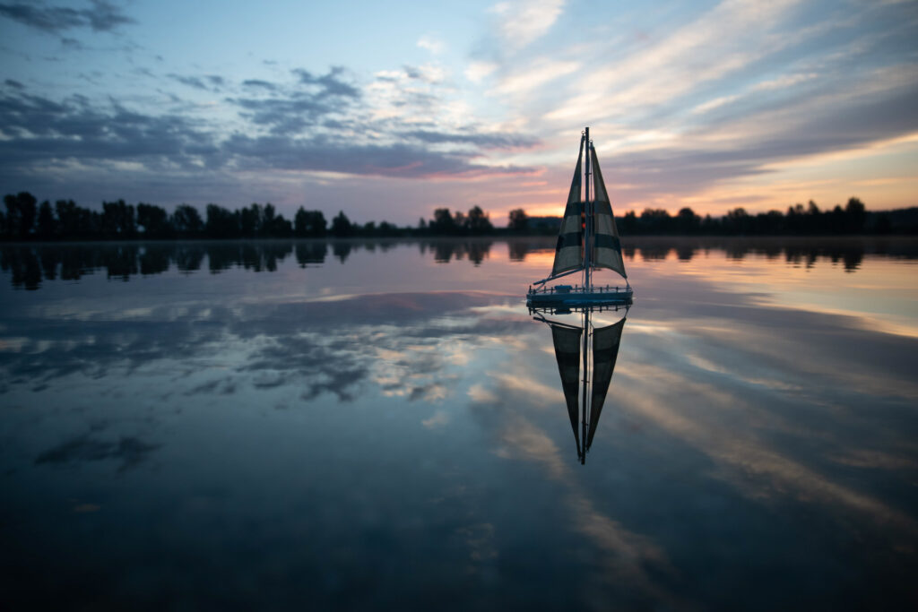 sailboat on a quiet lake reflecting sunrise
