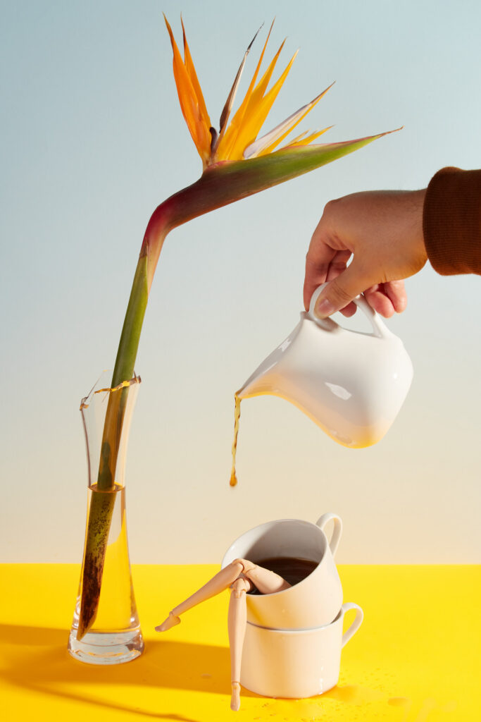 coffee being poured into a cup with doll legs, next to bird of paradise flower. All on a bright yellow table cloth