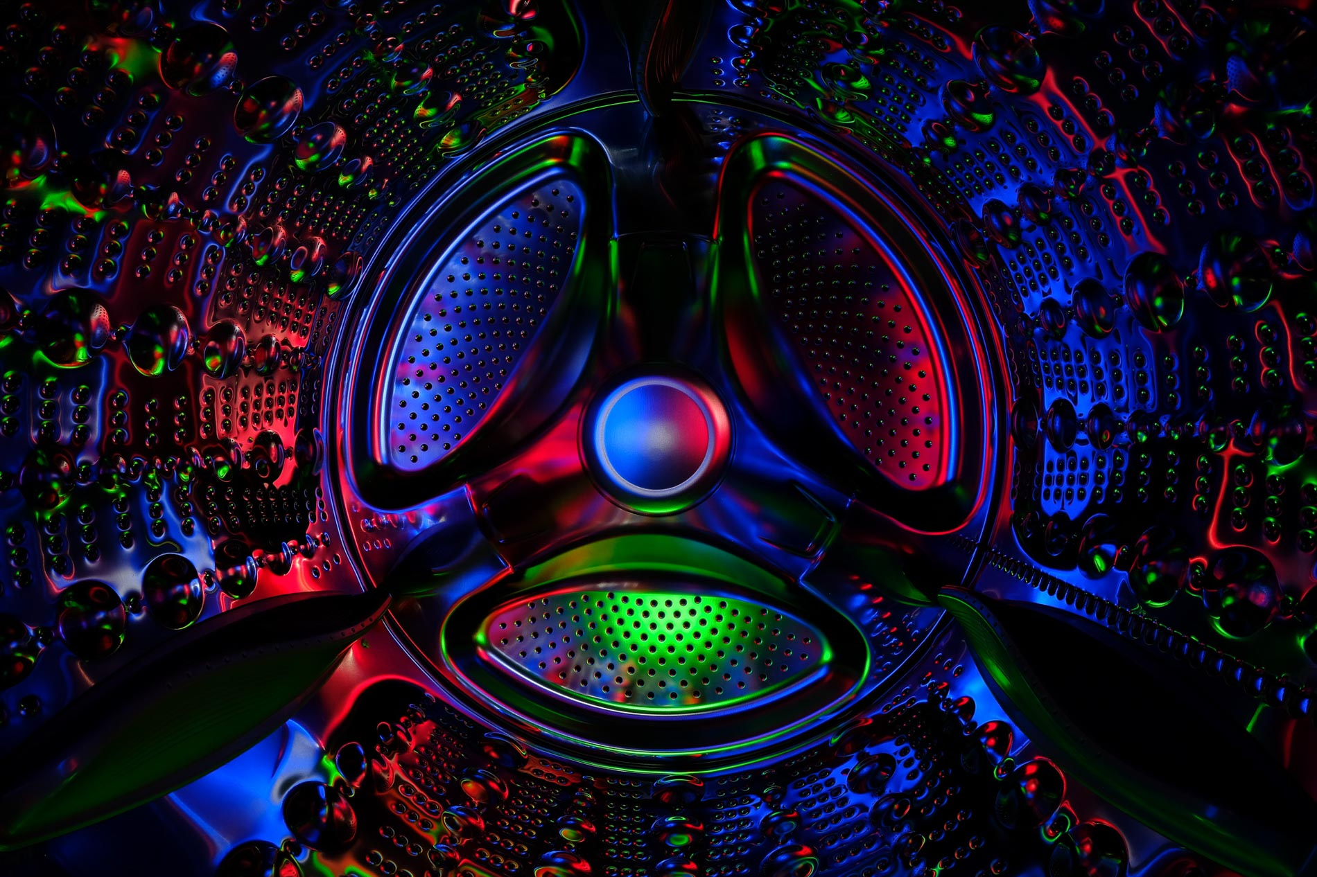 abstract inside of a clothes dryer lit by blue, red and green lights