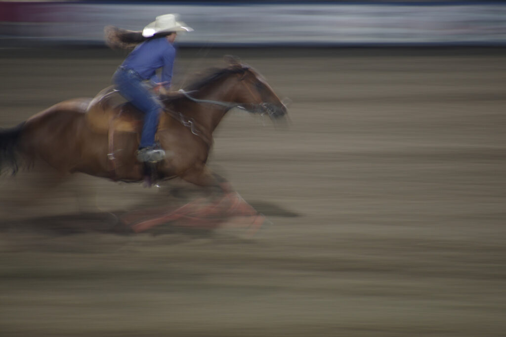 Woman on running horse in rodeo