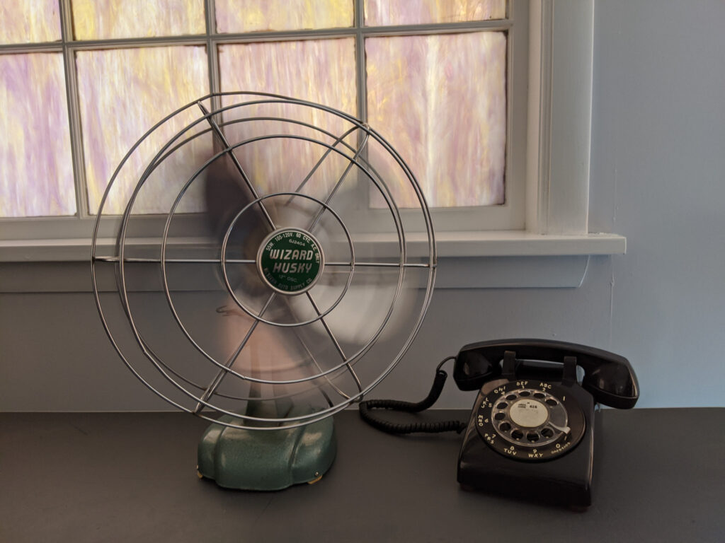 old fashioned fan and rotary dial phone on desk by window