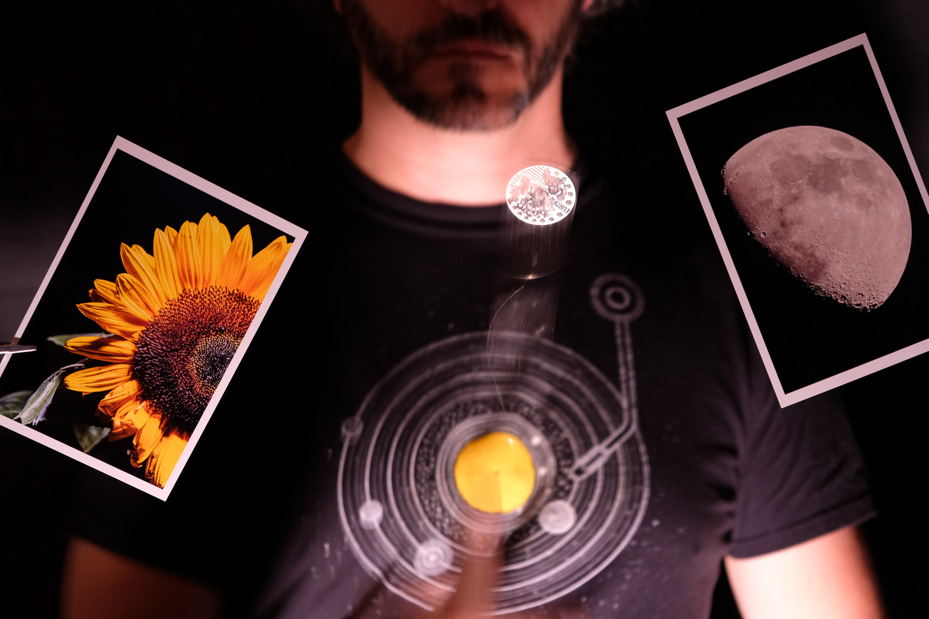 Man wearing tshirt with solar system, holding photos of sunflower and moon, photography by Maayan Windmuller