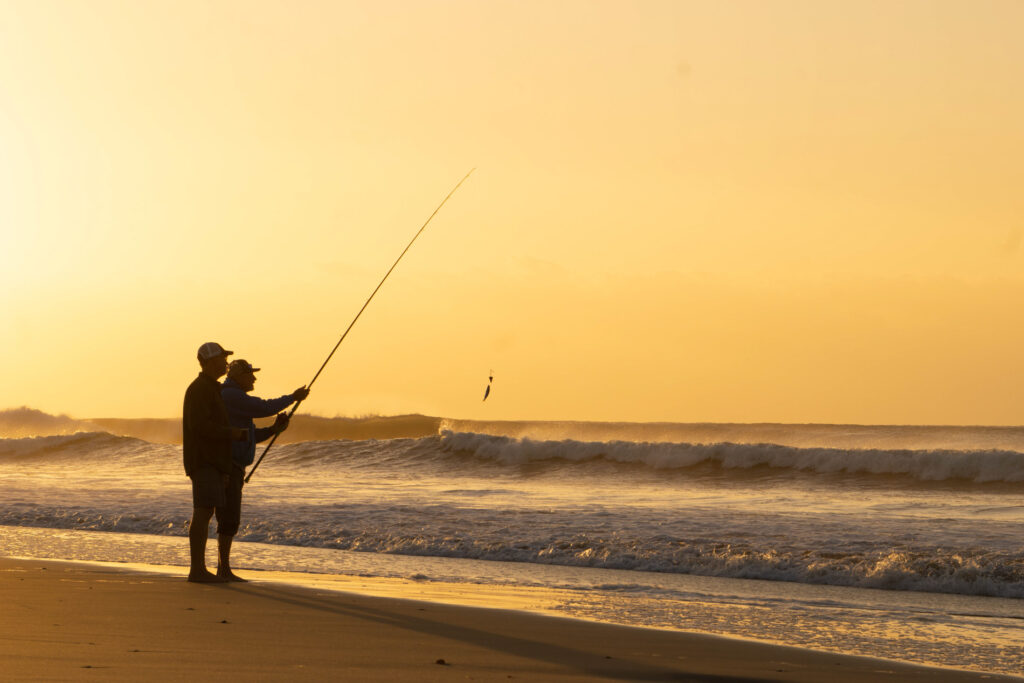 two people fishing on the ocean shore at sunset