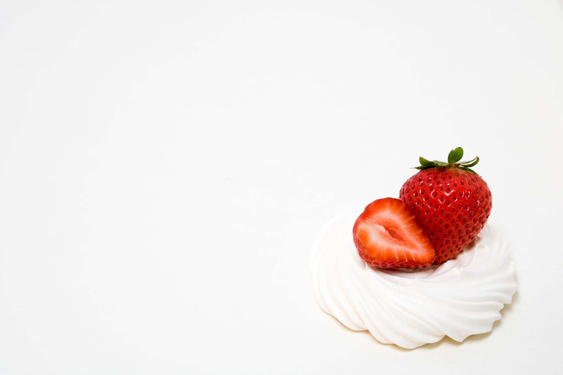 strawberries on whipped cream on a white background