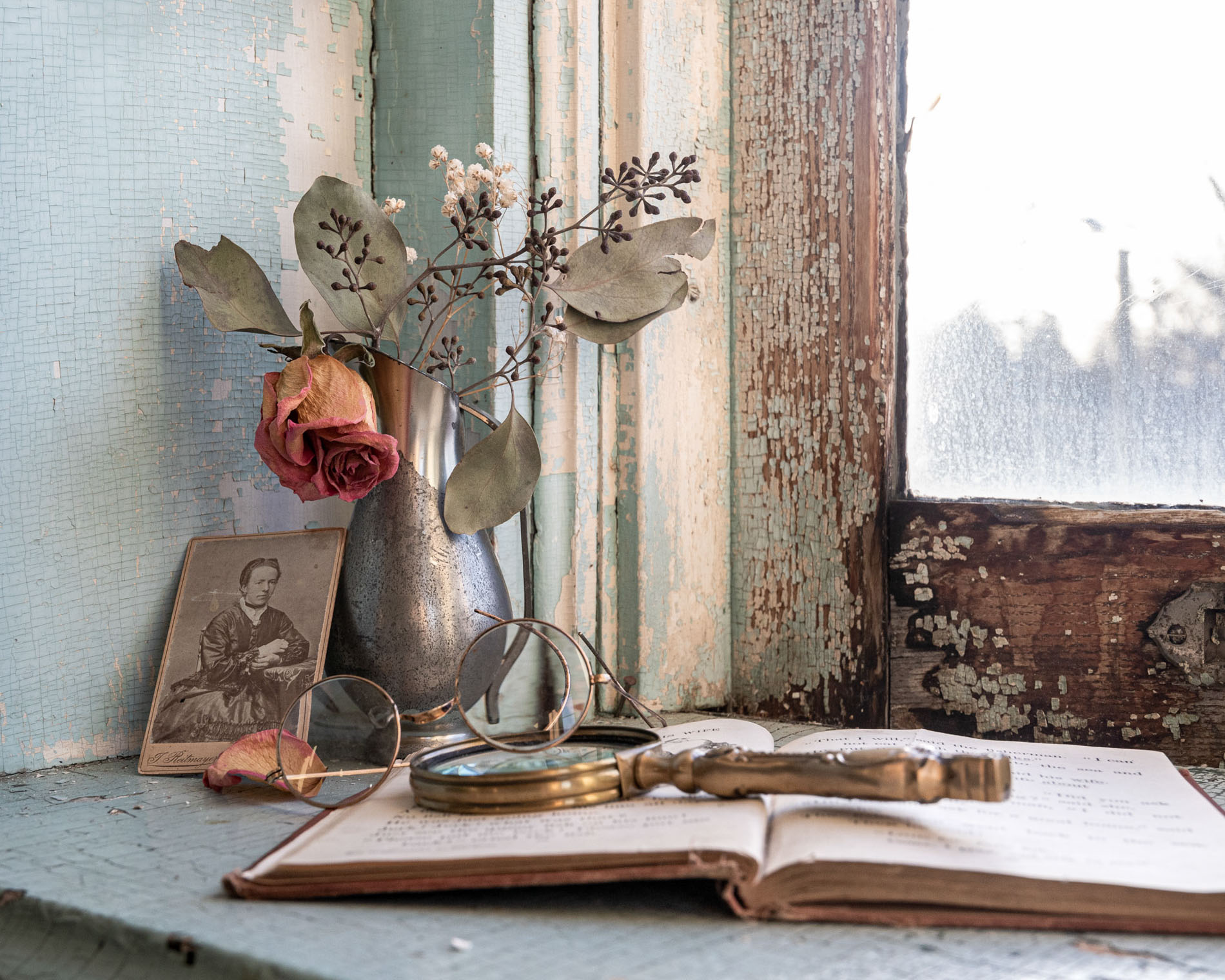 faded rose, photo and antique magnifying glass in front of an old window