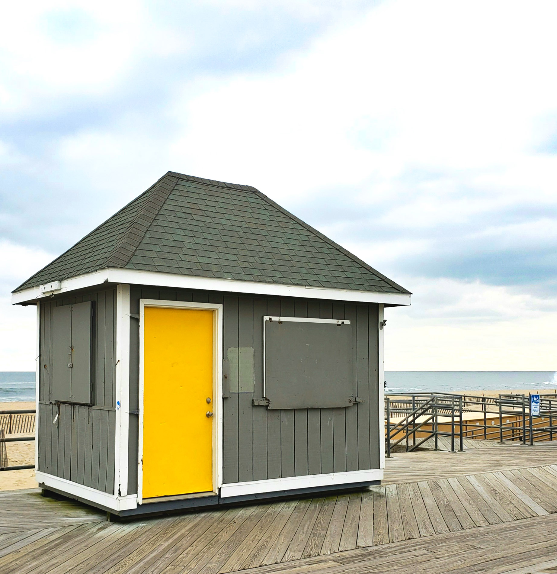 Grey shack with yellow door in front of ocean on partly cloudy day