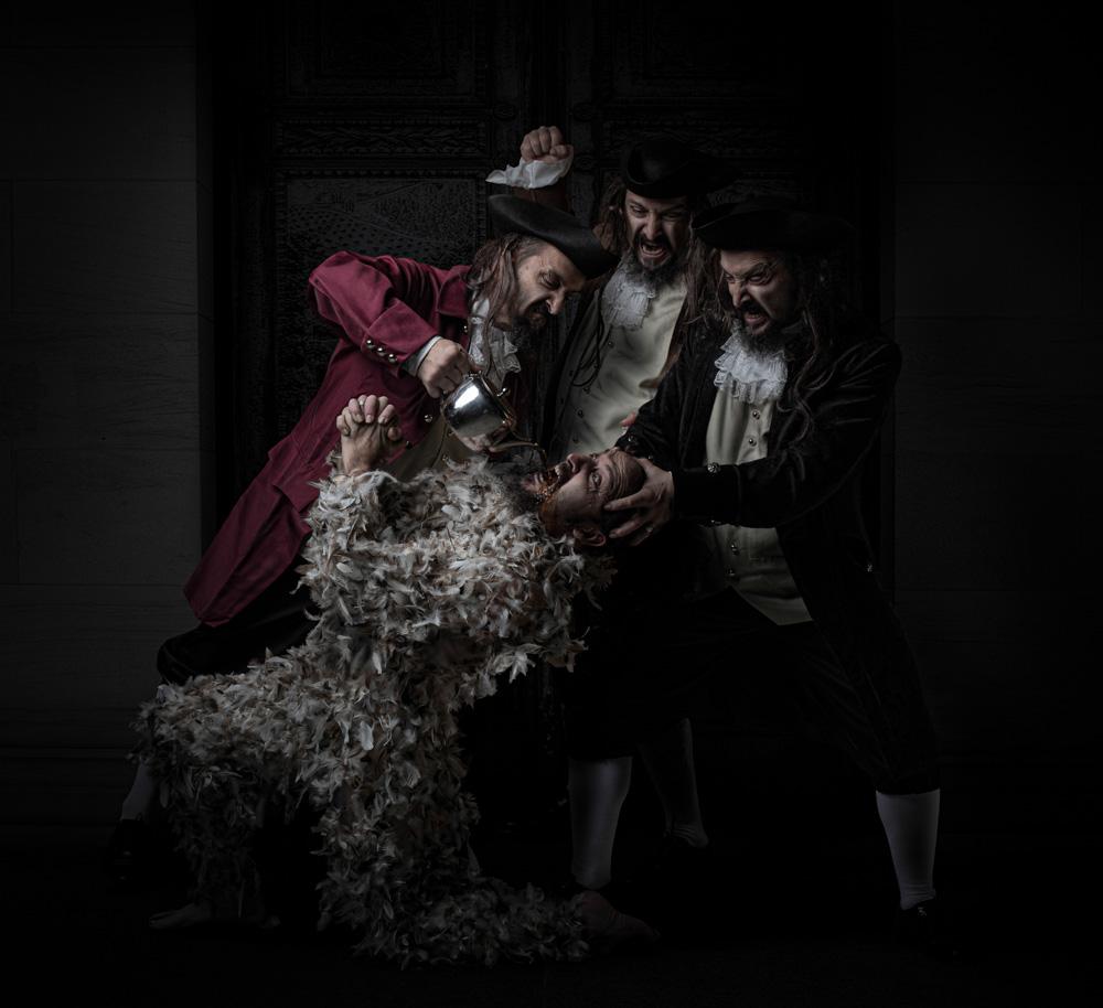 3 men force feeding a 4th feathered man tea